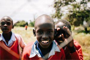 enfants africains regardent à travers d'une grille
